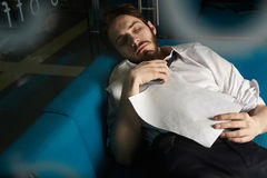 Hard day night. Overworked banker with smartphone and paper asleep on sofa in his office Stock Image