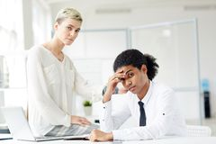 Hard day. Upset intercultural colleagues looking at camera during work in office Royalty Free Stock Photo