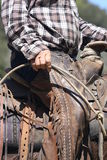 Hard days work. Old cowboy hand holding rope and in old saddle Stock Photos