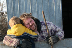 After a Hard Days Work. Son giving his dad a hug after a long days work stock photos