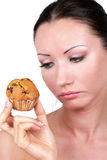 Hard diet choice. Woman with Hard diet choice looking at tasty cake in hand Royalty Free Stock Photography