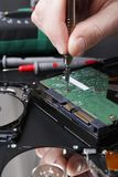 Hard disc drive disassembling close up. Repairman opening hdd for recovery information, service center and electronics repair concept Stock Image