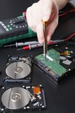 Hard disc drive disassembling close up. Repairman opening hdd for recovery information, service center and electronics repair concept Stock Images
