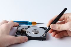 Hard disc drive disassembling close up. Repairman opening hdd fo. R recovery information, service center and electronics repair concept Royalty Free Stock Photography