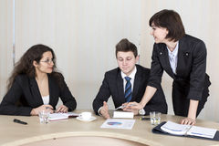 Hard discussion. Two female business ladies try to convince male boss about the subject, using printed charts and other office items stock photography