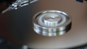 Hard Disk Drive, computer data storage, mirror surface The disc rotates the heads slid by the working surfaces, then the heads are. Parked and the disk stops stock footage
