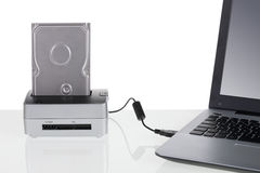 Hard disk drive with docking station connected to a laptop computer. Stock Image