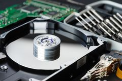 Disassembled hard disk drive inside close-up, spindle, actuator arm, read write head, platter, disassembly tools stock image
