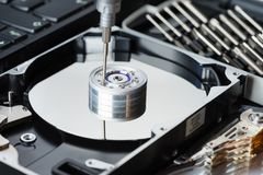 Disassembled hard disk drive inside close-up, spindle, actuator arm, read write head, platter, disassembly tools royalty free stock image