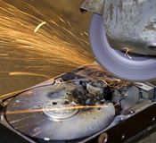 Hard disk grinding. Hard disk drive with rotating grinder and sparks in front of rusty back Royalty Free Stock Images