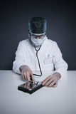 Hard Disk Healthcare. Doctor or Technician wearing a lab coat and stethoscope examining an hard disk Royalty Free Stock Photos