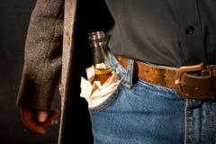 Hard drinker hiddes a bottle Royalty Free Stock Images