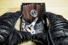 The hard drive from the computer in the hands  on a wooden surfa Royalty Free Stock Image
