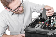 Hard drive connect. Engineer connects the SSD hard drive to the computer Royalty Free Stock Photos