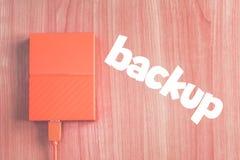 Hard drive. Portable external hard drive on the desk next to inscription `BACKUP royalty free stock photos