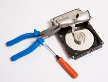 Hard drive and tools. Details of the covering of a computer hard drive curled back and hardware tools nearby.  White background Royalty Free Stock Image