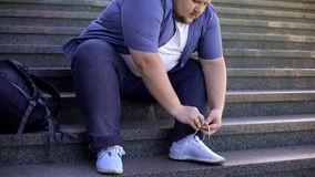 Hard for fat young man to tie shoelaces, challenges obese people face every day. Stock photo royalty free stock photo