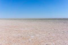 Hard flat surface of salt pan stretching to horizon Royalty Free Stock Image
