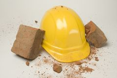 Hard hat-01. Depiction of a hardhat breaking the fall of a brick Stock Photos