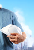 Hard hat. The strong hand holds a protective helmet Royalty Free Stock Photography