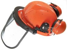 Hard Hat. Dirty hard hat with ear defenders and face mask  for protect while using a chain saw Royalty Free Stock Photo