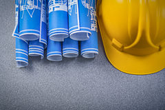 Hard hat blue rolled construction plans on grey background Royalty Free Stock Images