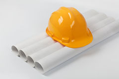 Hard hat on blueprint rolls Royalty Free Stock Images