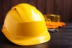 Hard hat and blurred safety equipment on background. Space for text royalty free stock images