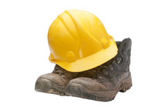 Hard Hat And Boots. A construction workers hard hat and boots fresh of a construction site and  still covered in grime, isolated on a white background Royalty Free Stock Photos
