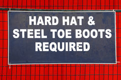 Hard Hat and Boots Required Sign. A sign on a construction site requires a hard hat and steel toe boots stock photos