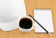 Hard hat, coffee cup and note pad Royalty Free Stock Photos