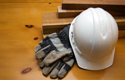 Hard Hat Construction. White hard hat and gloves resting against lumber Royalty Free Stock Photography