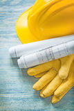 Hard hat construction plans protective gloves on wooden board bu Royalty Free Stock Photography