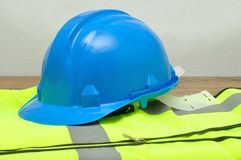 A hard hat displayed on a safety vest. Isolated on a wooden background Royalty Free Stock Images