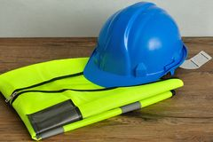 A hard hat displayed on a safety vest. Isolated on a wooden background Royalty Free Stock Photos