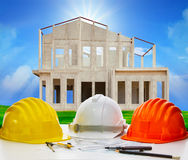 Hard hat of engineering on working table with plan and writing t Royalty Free Stock Image
