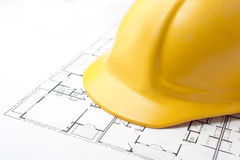 Hard Hat on Floor Plans. On Brightly Lit White Background Royalty Free Stock Photos