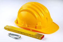 Hard hat with folded ruler Stock Photos