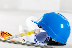 Hard hat, glasses and blueprints at construction site. Royalty Free Stock Image