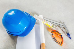 Hard hat, glasses and blueprints at construction site. Royalty Free Stock Photo