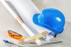 Hard hat, glasses and blueprints at construction site. Royalty Free Stock Photography