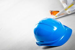 Hard hat, glasses and blueprints at construction site. Royalty Free Stock Images