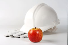 Hard hat , gloves and apple Stock Images