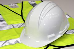 Hard Hat and Hi Vis Vest. White hard hat and yellow hi vis vest royalty free stock photography