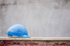 Hard hat on house building construction site. Blue hard hat on house building construction site Royalty Free Stock Photography