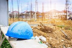 Hard hat on house building construction site. Blue hard hat on house building construction site Royalty Free Stock Images