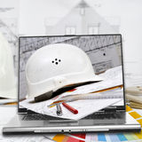 Hard hat, house plans and laptop Royalty Free Stock Image