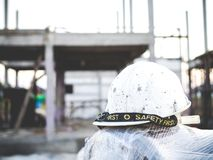 Hard hat with house under construction. Background royalty free stock photo