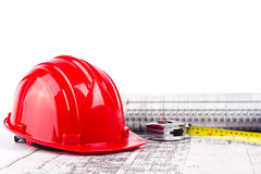 Hard hat measuring on blueprint Royalty Free Stock Photos