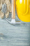 Hard hat pair of protective gloves claw hammer nails on wooden b Stock Photography
